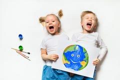 Concetto di ecologia con due bambini prety che dipingono terra su fondo bianco immagini stock