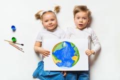 Concetto di ecologia con due bambini prety che dipingono terra triste su fondo bianco fotografia stock