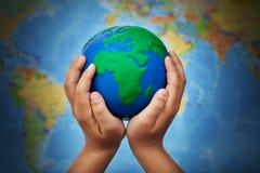 Concetto di ecologia con terra in mani del bambino immagini stock libere da diritti