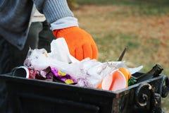 Concetto di ecologia e protezione del pianeta da detriti Il volontario pulisce l'immondizia nel parco e la getta nella pattumiera fotografia stock libera da diritti