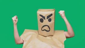 Concetto di emozione, gesti un uomo con un pacchetto sulla sua testa, con un aggressivo sorridente dipinto, arrabbiato fotografia stock libera da diritti