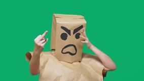 Concetto di emozione, gesti un uomo con un pacchetto sulla sua testa, con un aggressivo sorridente dipinto, arrabbiato fotografie stock