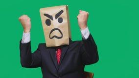 Concetto di emozione, gesti un uomo con un pacchetto sulla sua testa, con un aggressivo sorridente dipinto, arrabbiato fotografia stock