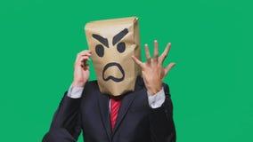 Concetto di emozione, gesti un uomo con un pacchetto sulla sua testa, con un aggressivo sorridente dipinto, arrabbiato parlando s fotografie stock libere da diritti