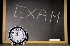 Concetto di esame, iscrizione sulla lavagna ed orologio Immagini Stock