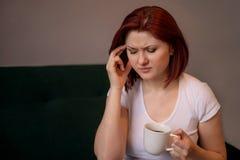 Concetto di esaurimento, di sforzo, di emicrania o di emicrania: la donna con taglio di capelli del peso si siede sul sofà con la immagine stock