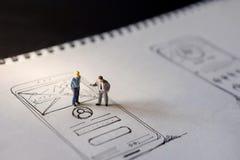 Concetto di esperienza utente presente da una figura di due miniature di Busi fotografie stock libere da diritti