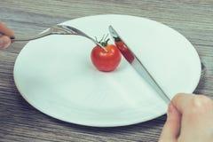 Concetto di essere a dieta rigoroso Il ` s della donna passa la prova di tagliare poco ch immagini stock