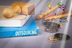 Concetto di esternalizzazione libro blu su una tavola grigia dell'ufficio immagine stock