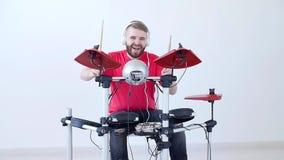 Concetto di fabbricazione di musica e di hobby Giovane che gioca i tamburi a casa o in uno studio di registrazione video d archivio