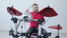 Concetto di fabbricazione di musica e di hobby Giovane che gioca i tamburi a casa o in uno studio di registrazione stock footage