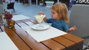 Concetto di felicità dei bambini di infanzia del bambino Ragazzo dolce del bambino che mangia il gelato Gelato in caffè archivi video