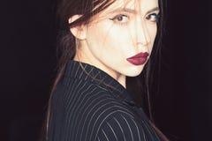Concetto di femminilità Ragazza sul fronte sicuro rigoroso in rivestimento nero, fondo nero Donna con trucco alla moda e fotografia stock