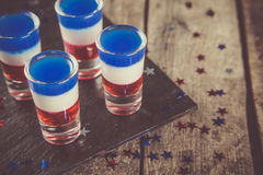 Concetto di festa dell'indipendenza - la bandiera ha colorato i brevi cocktail su fondo rustico Fotografia Stock
