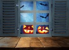 Concetto di festa di Halloween Tavola rustica vuota davanti al fondo frequentato del cielo notturno ed alla vecchia finestra Aspe fotografie stock libere da diritti