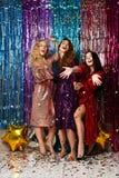 Concetto di feste e del partito Tre donne del fascino negli zecchini di lusso di scintillio vestono divertiresi fotografie stock libere da diritti