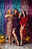 Concetto di feste e del partito Tre donne del fascino negli zecchini di lusso di scintillio vestono divertiresi fotografia stock libera da diritti
