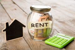 Concetto di finanza del bene immobile - vetro dei soldi con la parola di affitto Fotografia Stock
