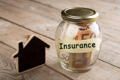 Concetto di finanza del bene immobile - vetro dei soldi con la parola di assicurazione Fotografia Stock Libera da Diritti