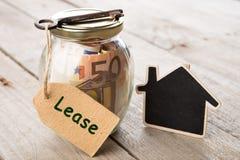 Concetto di finanza del bene immobile - vetro dei soldi con la parola del contratto d'affitto Immagini Stock Libere da Diritti