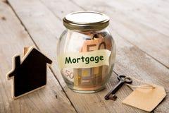 Concetto di finanza del bene immobile - vetro dei soldi con la parola di ipoteca Immagine Stock