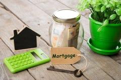 Concetto di finanza del bene immobile - vetro dei soldi con la parola di ipoteca Fotografia Stock Libera da Diritti