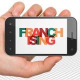Concetto di finanza: Mano che tiene Smartphone con il franchising sull'esposizione Fotografie Stock Libere da Diritti