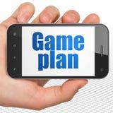 Concetto di finanza: Mano che tiene Smartphone con il piano tattico su esposizione Immagini Stock Libere da Diritti