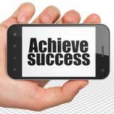 Concetto di finanza: Passi la tenuta dello Smartphone con raggiungono il successo su esposizione Fotografia Stock Libera da Diritti
