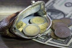 Concetto di finanze Portafoglio d'annata con le euro monete e banconote in dollari su fondo di legno Fotografia Stock