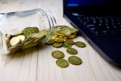 Concetto di finanziamento Monete dorate con il contenitore di vetro ed il computer portatile Fotografia Stock