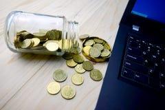 Concetto di finanziamento Monete dorate con il contenitore di vetro ed il computer portatile Fotografie Stock Libere da Diritti