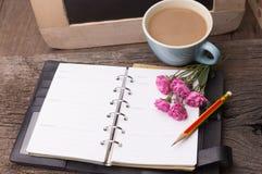 Concetto di fine settimana Rosa di rosa, tazza con caffè, diario e matita sopra Immagine Stock