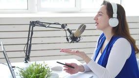 Concetto di flusso continuo e di radiodiffusione Cuffie d'uso della giovane donna e parlare alla stazione radio online video d archivio