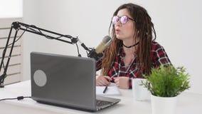 Concetto di flusso continuo e di radiodiffusione La giovane donna nello studio parla in un microfono stock footage