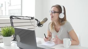 Concetto di flusso continuo e di radiodiffusione La giovane ragazza allegra nello studio parla in un microfono stock footage