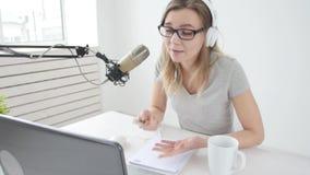 Concetto di flusso continuo e di radiodiffusione La giovane ragazza allegra nello studio parla in un microfono archivi video