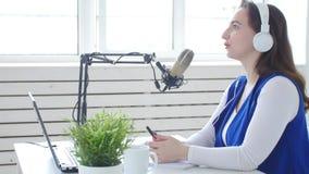 Concetto di flusso continuo e di radiodiffusione La giovane ragazza allegra nello studio parla in un microfono video d archivio