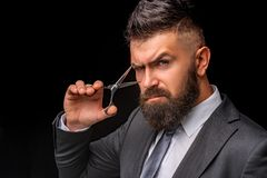 Concetto di forbici Uomo barbuto, pantaloni a vita bassa barbuti Barba alla moda dell'uomo Forbici del barbiere Parrucchiere d'an fotografia stock libera da diritti