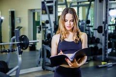 Concetto di forma fisica, di allenamento, della palestra, di tecnologia e di stile di vita - giovane donna che tiene una lavagna  Fotografia Stock
