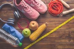 Concetto di forma fisica con l'attrezzatura di esercizio e l'alimento sano su fondo di legno Fotografie Stock Libere da Diritti