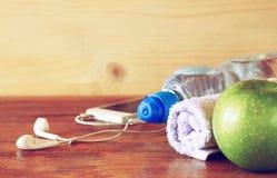 Concetto di forma fisica con la bottiglia di acqua, telefono cellulare con le cuffie Fotografia Stock