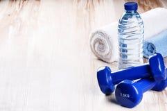 Concetto di forma fisica con le teste di legno e la bottiglia di acqua Fotografia Stock