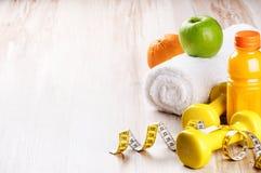 Concetto di forma fisica con le teste di legno e la frutta fresca Fotografie Stock