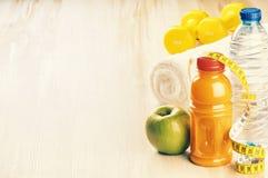 Concetto di forma fisica con le teste di legno, la mela verde e la bottiglia di acqua Fotografia Stock Libera da Diritti