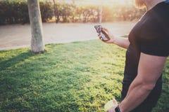 Concetto di forma fisica di allenamento Atleta bello muscolare che controlla il programm di addestramento sull'applicazione dello Fotografie Stock