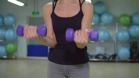 Concetto di forma fisica Giovane donna castana con le teste di legno nella palestra video d archivio