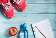 Concetto di forma fisica, scarpe da tennis rosa, mela rossa, bottiglia di acqua e taccuino con la matita su fondo di legno, vista fotografia stock libera da diritti