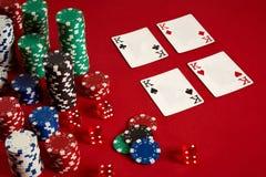 Concetto di gioco dell'attrezzatura e di spettacolo del poker del casinò - vicino su delle carte da gioco e dei chip a fondo ross Fotografie Stock