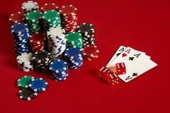 Concetto di gioco dell'attrezzatura e di spettacolo del poker del casinò - vicino su delle carte da gioco e dei chip a fondo ross Immagini Stock